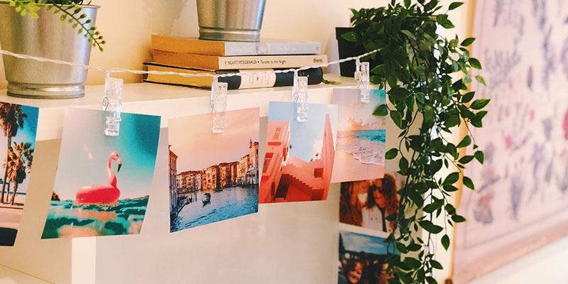 квадратные фотографии на веревке рядом скнигами и цветами